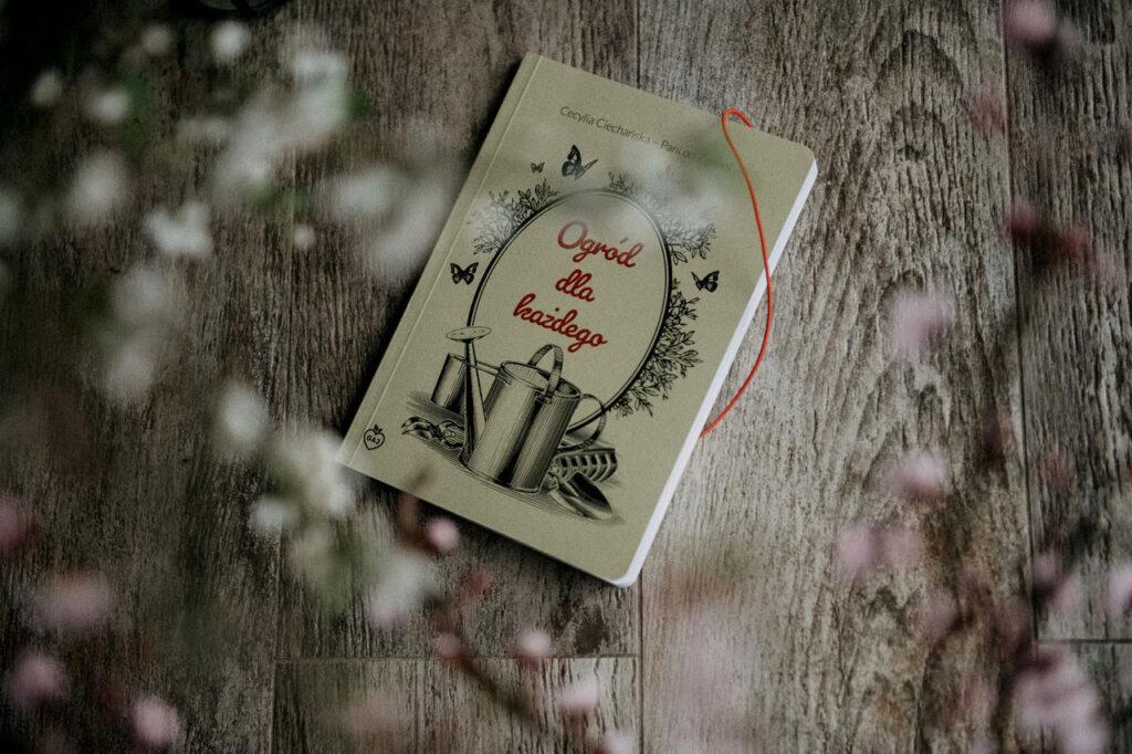 Książka a na pierwszym planie rozmazane kwiaty