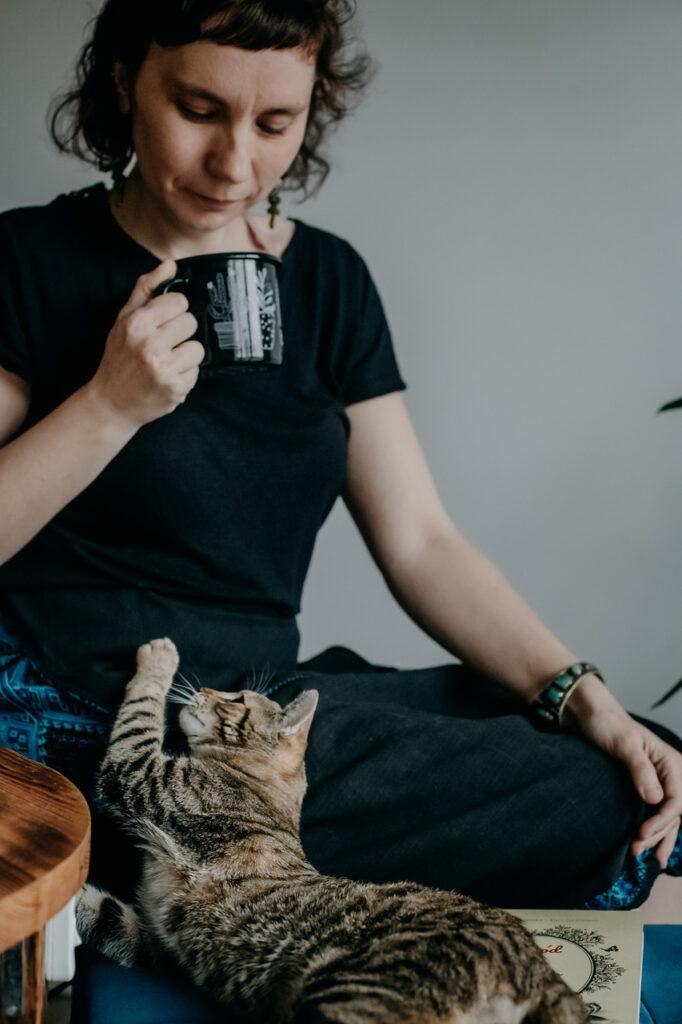 Kobieta trzymająca kubek a w jej nogach leży kotek