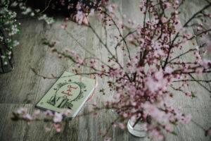 książka położona na podłodze obok kwiaty na gałązkach w wazonie