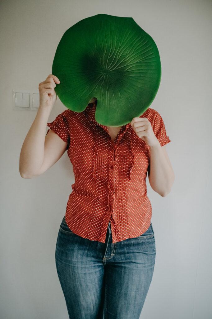 Kobieta z wielkim zielonym liściem prysłaniającym twarz